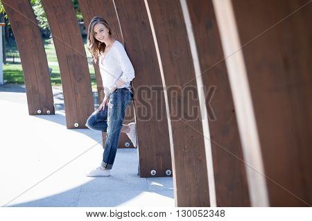Pretty young woman having fun in the park alley.