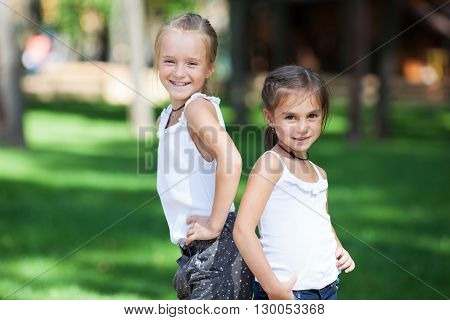 Wonderful happy girls standing on the lawn in the park. Girls seven years.