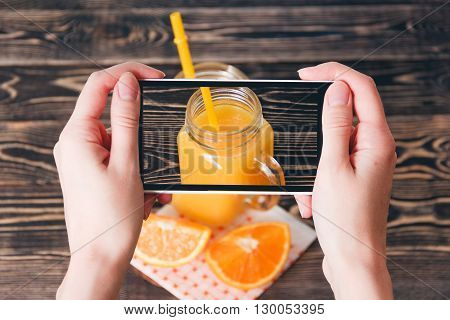 Hands Taking Photo of Juice and Oranges on Wooden Background. Technology Concept