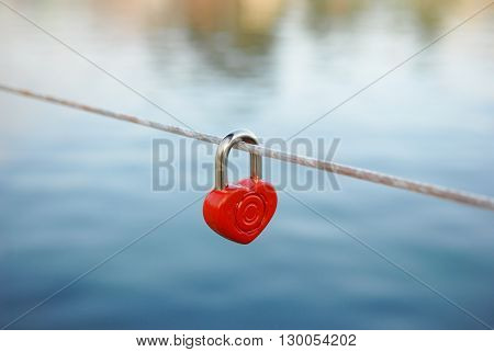 lock  in the form of heart hanging on a rope over the water