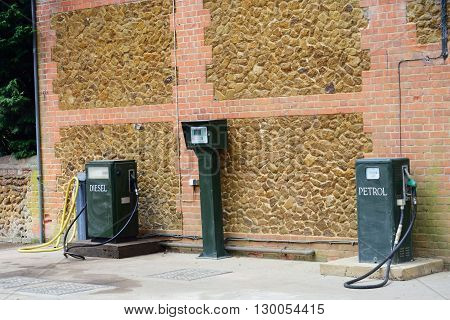 Vintage green petrol pumps with brick wall in background