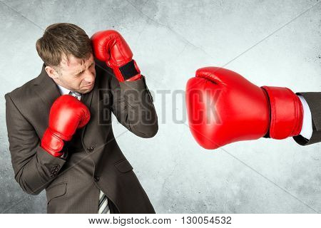 Businessman in boxing gloves against big red boxing glove