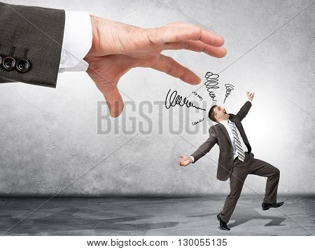 Business boss hand catching scared employee on grey wall background