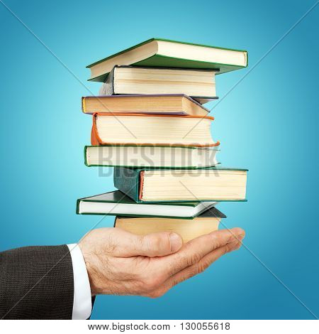 Business man holding stack of books on blue background