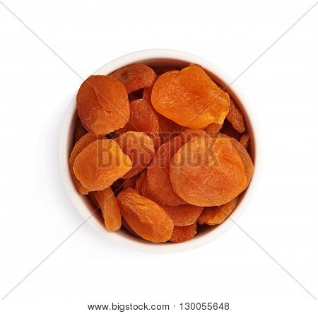 Dried orange apricots in ceramic bowl over isolated white background, top view