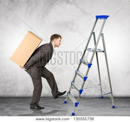 Middle aged business man with difficult task going up ladder