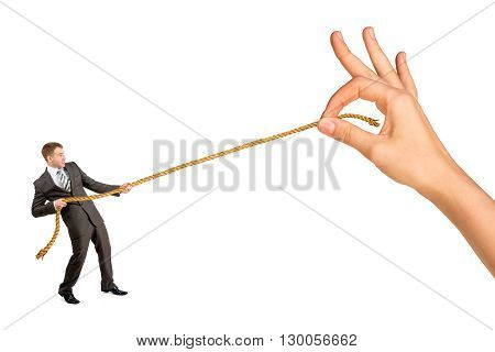 Businessman pulling rope against big woman hand isolated on white background
