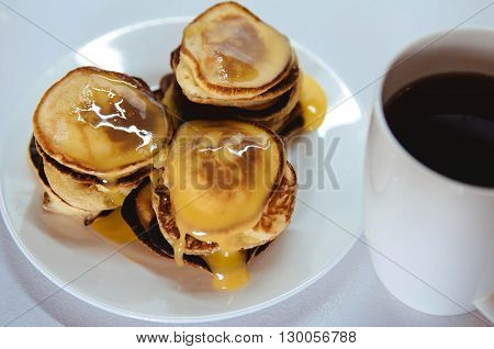 homemade pancakes with honey on a white plate on a white background