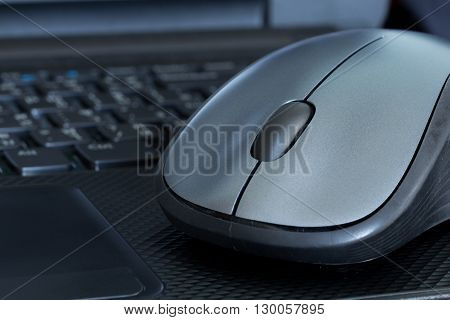 Silver mouse on black laptop. It's a working equipment in nowaday.