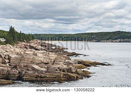 Rocky coastline and Newport Cove beach in Acadia National Park under heavy clouds