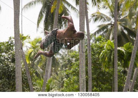 KOH PHANGANTHAILAND - NOVEMBER 25 2014 : Unidentified man jump in the pool in the attraction Slip N Fly on island Koh Phangan