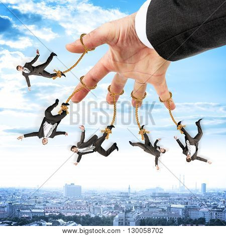 Image of businessmen hanging on strings like marionette. Conceptual photography