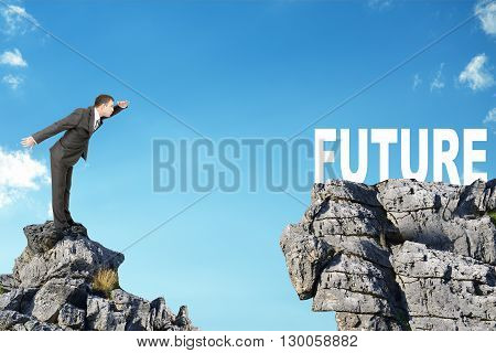 Young businessman standing on edge of rock mountain and looking at word future