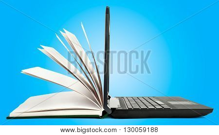 Book and open laptop on blue background
