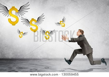 Business man running to catch flying dollar sign on gray background