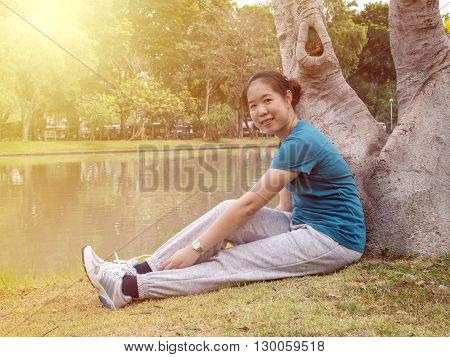 One women smile and sit under the tree with feel relax and happiness at the garden under sunlight in the morning with warm / soft color tone