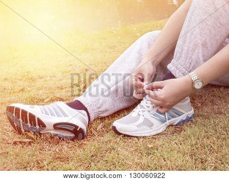 One women sit on grass and tying shoelaces at the garden under sunlight in the morning with warm / soft color tone