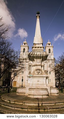Statue and church  in the city of Lisbon Portugal