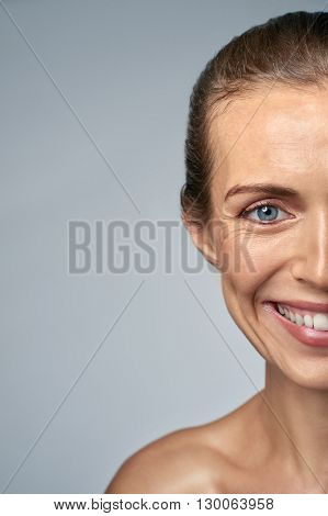 Close up portrait of smiling woman in her 30s, showing fine wrinkles and aging