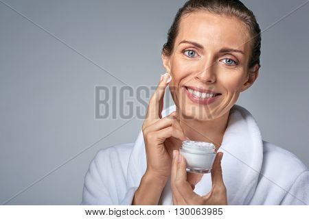 portrait of elegant middle age woman in bathrobe applying face cream, jar in her hand