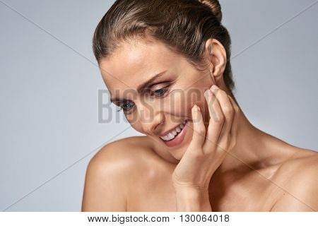 Middle age beauty model looking down in studio, healthy mature woman