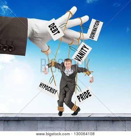 Image of businessman hanging on strings like marionette with words. Conceptual photography