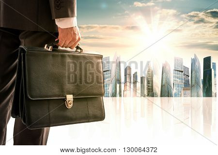 Businessman with suitcase against morning modern city, rear view