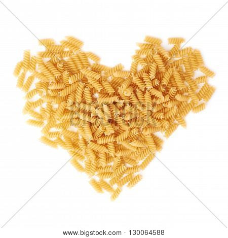 Heart shape made of dry rotini yellow pasta over isolated white background