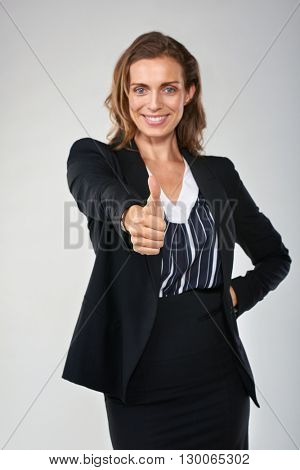 Beautiful businesswoman giving the thumbs up hand gesture, approval praise good job concept