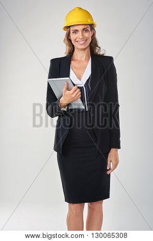Woman wearing hardhat safety helmet holding tablet device, architect surveyor engineer professional