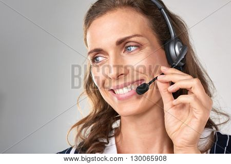 Portrait of smiling cheerful customer support female phone worker, against grey background. Consulting and assistance service call center