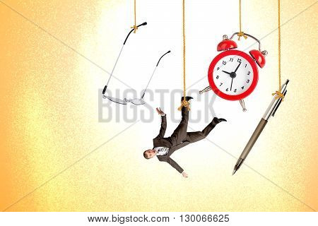 Man hanging on rope with clock, pen and glasses on colorful background
