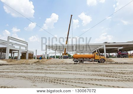 Mobile crane is carry concrete joist to assembly huge hall. Landscape transform into urban area with machinery people are working. View on construction site.