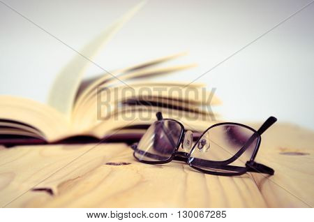 A pair of glasses on wooden table with an open book behind.