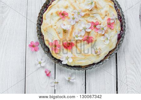 Top View on Fruit Pie with Flowers and Whipped Egg Whites on a Wood Table