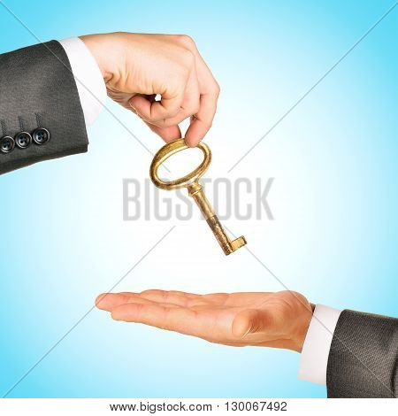 Gold key exchange between two businessmen on blue