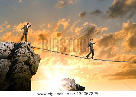 Conceptual image of businessman walking on rope above gap, sunset