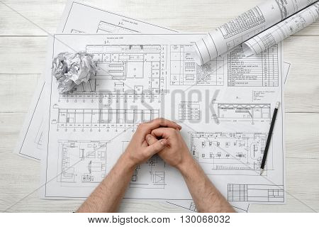 Top view of folded hands of man on wooden surface with architect drawing and hand-folding piece of paper. Close-up view. Workplace of architect or constructor. Engineering work. Construction and architecture.