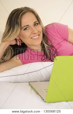 A woman laying in her bed with a big smile working on her laptop.