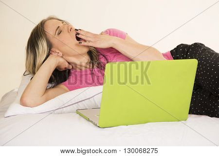 a woman laying in her bed working on her laptop getting really tired.