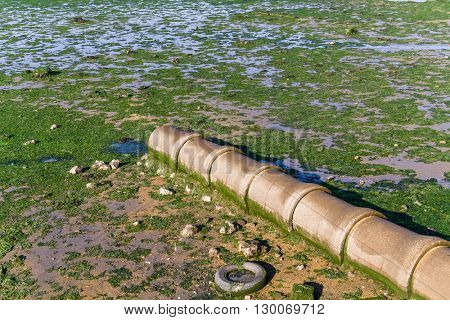 Open air sewer pipe draining to the Seixal Bay, a Tagus River branch near Lisbon, Portugal.