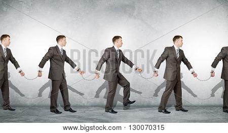 Businessmen in handcuffs arrested on grey background