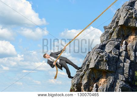 Young businessman scaling rock with rope, cloudscape