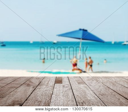 Wood table top on blurred blue sea with some people relax on the white sand beach - Can be used for display or montage your products