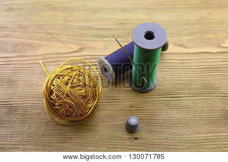 macro ball of gold threads threads and needle. a thimble on a wooden background