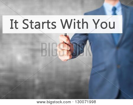 It Starts With You - Businessman Hand Holding Sign