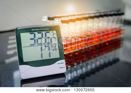 Digital hygro thermometer with blurred test tube in laboratory