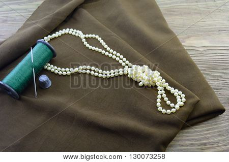 macro composition a necklace from pearls tied by knot lies on dark fabric near green threads a needle and a thimble. wooden background