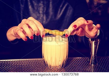 Female bartender is adding orange zest to cocktail, toned image