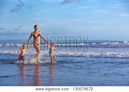 Happy barefoot family having fun - mother baby son daughter together run with splashes by water pool along surf of sunset sea beach. Active parent and people activity on summer holiday with children